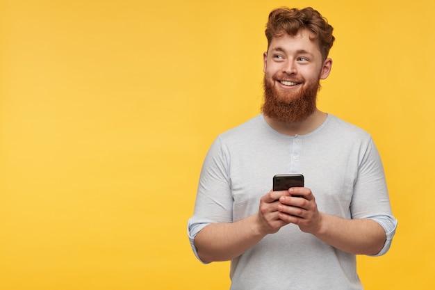 Giovane maschio di redhead con una grande barba sorride e tiene lo smartphone nelle sue mani. guardando da parte a destra nello spazio della copia su giallo