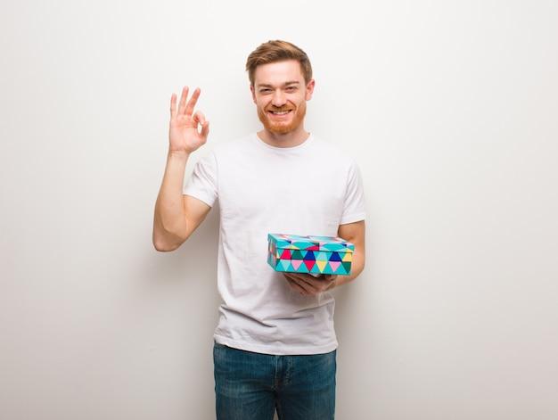 Giovane uomo di redhead che fa gesto giusto allegro e sicuro. in possesso di una scatola regalo.