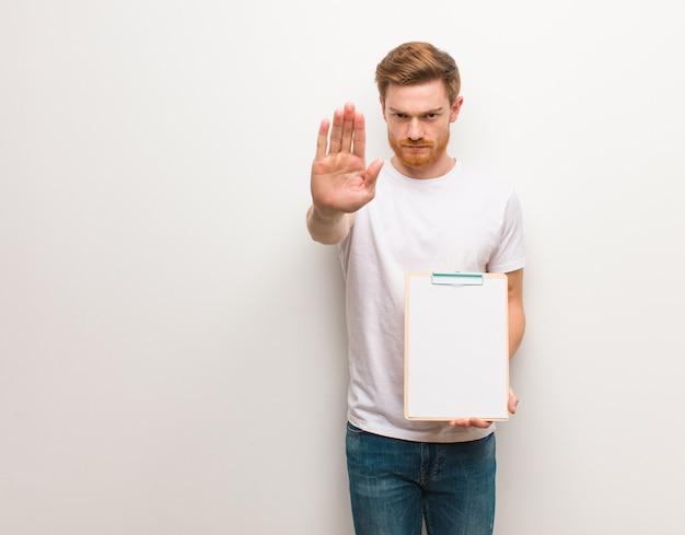 Giovane uomo di redhead che mette la mano nella parte anteriore. ha in mano un blocco per appunti.