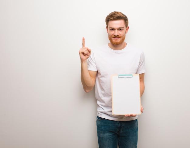 Giovane uomo di redhead che mostra numero uno. sta tenendo un blocco per appunti.