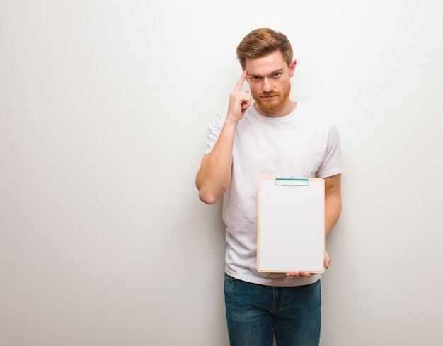 Giovane uomo di redhead che pensa ad un'idea sta tenendo un blocco per appunti.