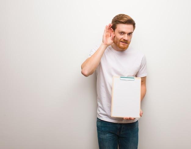 Il giovane uomo di redhead prova ad ascoltare un gossip. ha in mano un blocco per appunti.