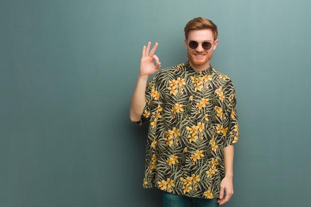 Il giovane uomo della testarossa che indossa l'estate esotica copre il gesto giusto facente allegro e sicuro
