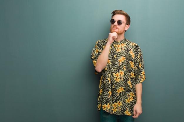 Il giovane uomo di redhead che indossa l'estate esotica copre dubitare e confuso