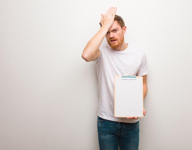 Giovane uomo di redhead preoccupato e sopraffatto. ha in mano un blocco per appunti.