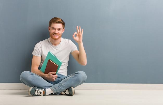 Giovane uomo dello studente della testarossa che si siede sul pavimento allegro e sicuro che fa gesto giusto