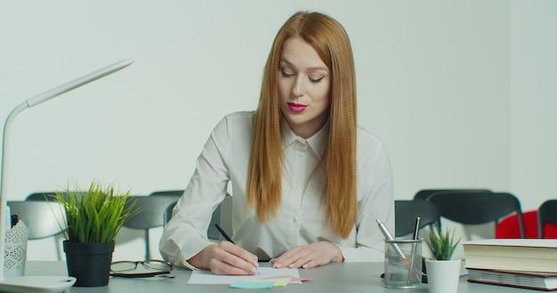 La giovane donna della testarossa in vetri ha chiamata in conferenza di affari in linea.