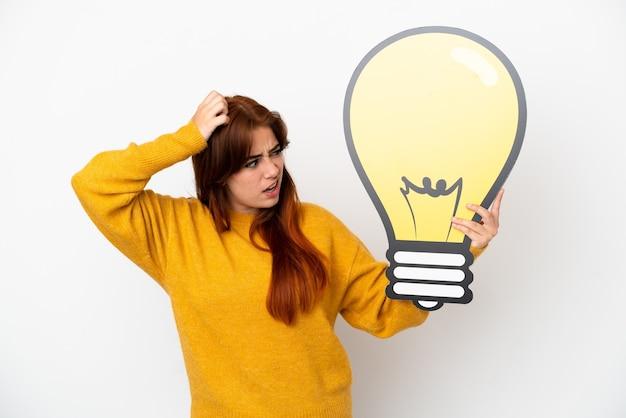 Giovane donna rossa isolata su sfondo bianco con in mano un'icona a forma di lampadina e dubbi