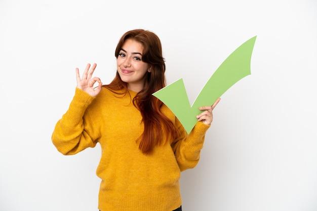 Giovane donna rossa isolata su sfondo bianco con in mano un'icona di spunta e facendo segno ok