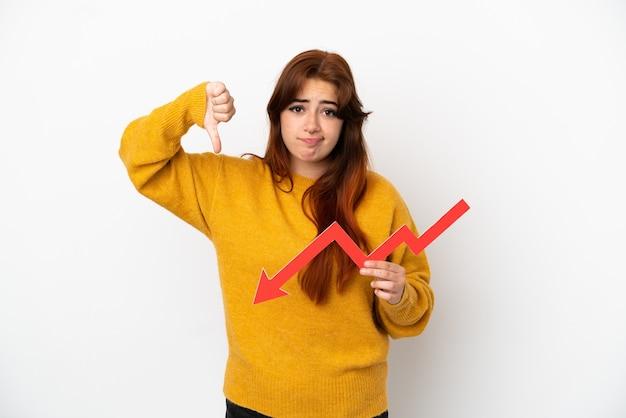 Giovane donna rossa isolata su sfondo bianco che tiene una freccia verso il basso e fa un cattivo segnale