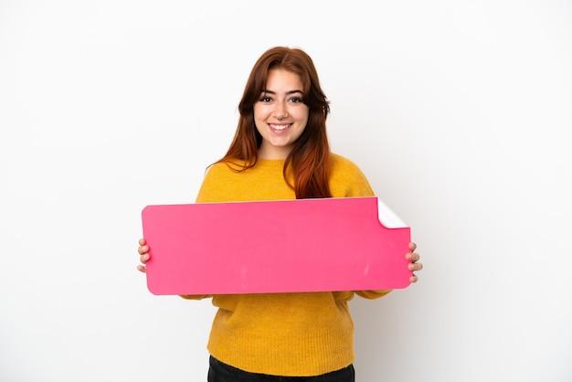 Giovane donna dai capelli rossi isolata su sfondo bianco con in mano un cartello vuoto