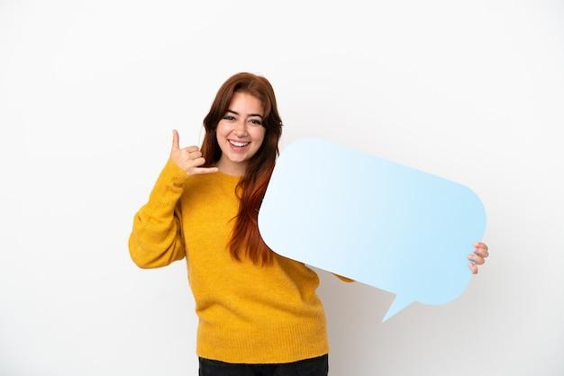 Giovane donna dai capelli rossi isolata su sfondo bianco che tiene un fumetto vuoto e fa il gesto del telefono