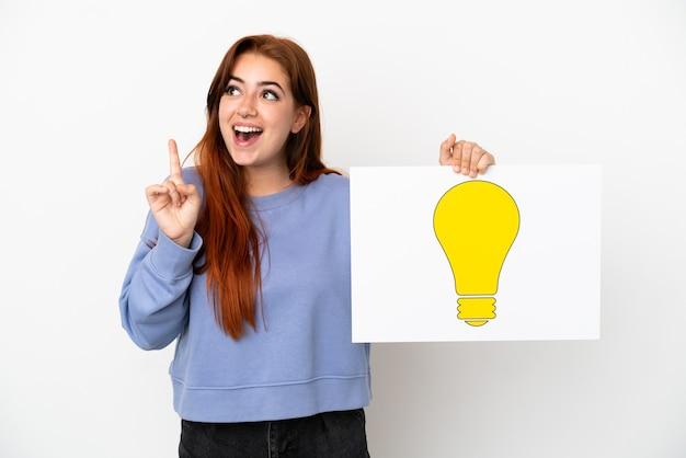 Giovane donna rossa isolata su fondo bianco che tiene un cartello con l'icona della lampadina e pensa