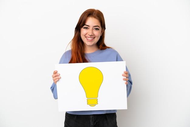 Giovane donna dai capelli rossi isolata su fondo bianco che tiene un cartello con l'icona della lampadina con espressione felice