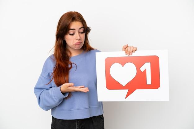 Giovane donna rossa isolata su sfondo bianco che tiene un cartello con l'icona mi piace e lo punta