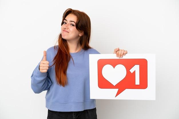 Giovane donna dai capelli rossi isolata su sfondo bianco con in mano un cartello con l'icona mi piace con il pollice in alto