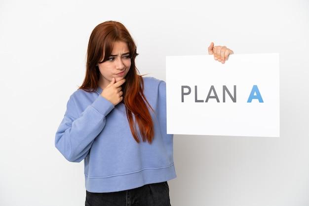 Giovane donna dai capelli rossi isolata su sfondo bianco con in mano un cartello con il messaggio piano a e pensando
