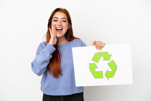 Giovane donna dai capelli rossi isolata su sfondo bianco con in mano un cartello con l'icona di riciclo e urlando