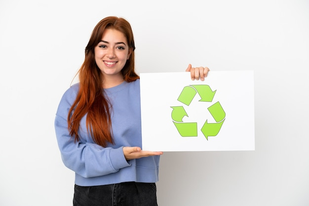 Giovane donna rossa isolata su sfondo bianco con in mano un cartello con icona di riciclo con espressione felice