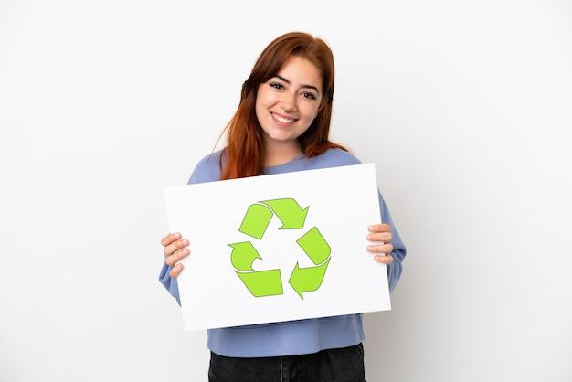 Giovane donna rossa isolata su sfondo bianco in possesso di un cartello con icona di riciclo con espressione felice