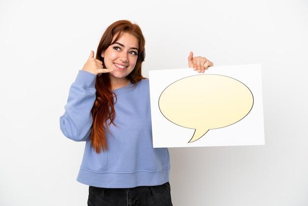 Giovane donna dai capelli rossi isolata su sfondo bianco che tiene un cartello con l'icona del fumetto e fa il gesto del telefono