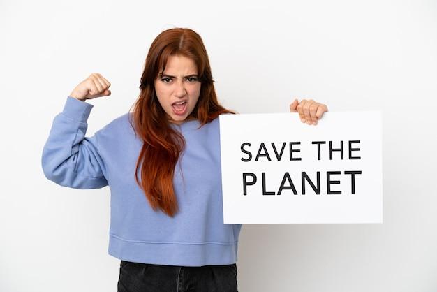 Giovane donna dai capelli rossi isolata su sfondo bianco che tiene un cartello con il testo salva il pianeta e fa un gesto forte