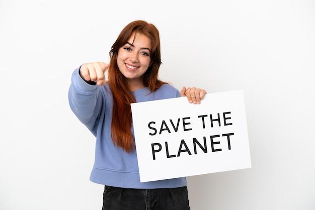Giovane donna dai capelli rossi isolata su sfondo bianco con in mano un cartello con il testo salva il pianeta e indicando la parte anteriore