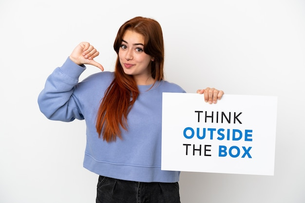 Giovane donna dai capelli rossi isolata su sfondo bianco con in mano un cartello con il testo pensa fuori dagli schemi con un gesto orgoglioso
