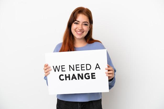 Giovane donna dai capelli rossi isolata su sfondo bianco con in mano un cartello con testo abbiamo bisogno di un cambiamento con espressione felice