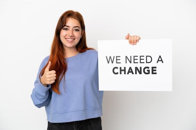 Giovane donna dai capelli rossi isolata su sfondo bianco con in mano un cartello con il testo abbiamo bisogno di un cambiamento con il pollice in alto