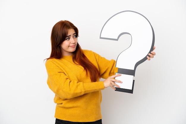 Giovane donna dai capelli rossi isolata su sfondo bianco che tiene un'icona del punto interrogativo