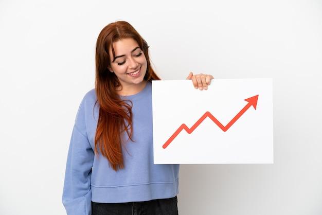 Giovane donna rossa isolata su sfondo bianco con in mano un cartello con un simbolo di freccia in crescita statistica e pensiero