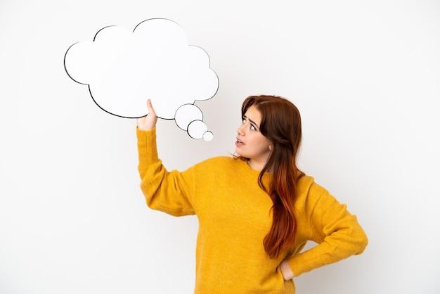 Giovane donna dai capelli rossi isolata su sfondo bianco con in mano un fumetto di pensiero