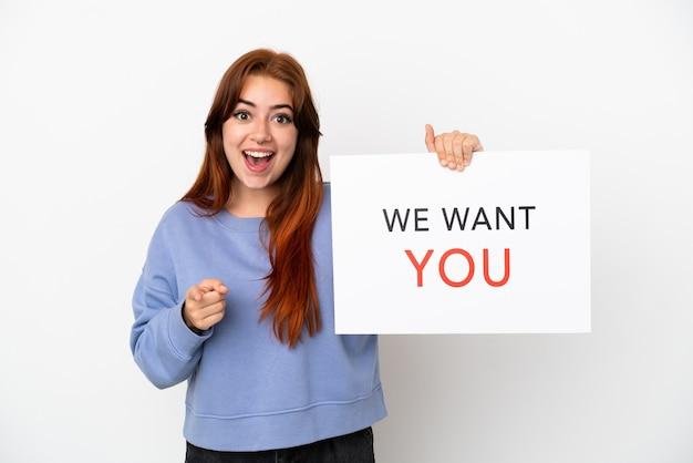 Giovane donna rossa isolata su sfondo bianco tenendo we want you board e indicando la parte anteriore