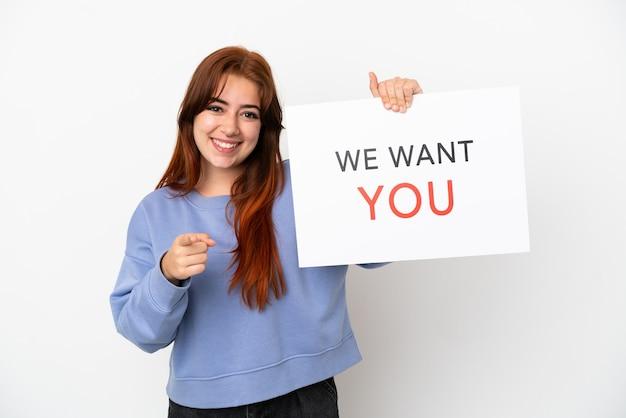 Giovane donna dai capelli rossi isolata su sfondo bianco tenendo we want you board e indicando la parte anteriore