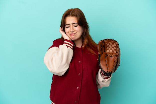Giovane donna dai capelli rossi che gioca a baseball isolata su sfondo blu frustrata e che copre le orecchie