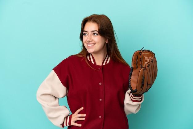 Giovane donna rossa che gioca a baseball isolata su sfondo blu in posa con le braccia all'anca e sorridente