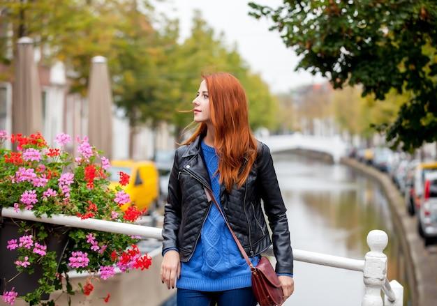 Giovane donna rossa in piedi in strada nella città di amsterdam in primavera.
