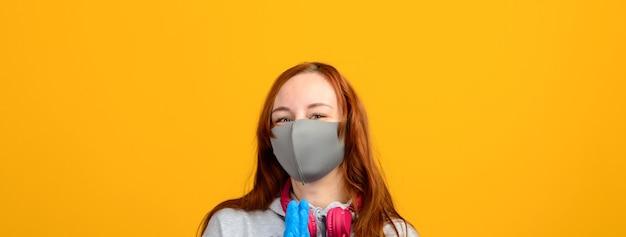 Giovane donna della testarossa che indossa una mascherina medica