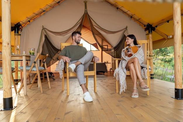 Giovane coppia rilassata seduta in poltrona sul patio della tenda glamping