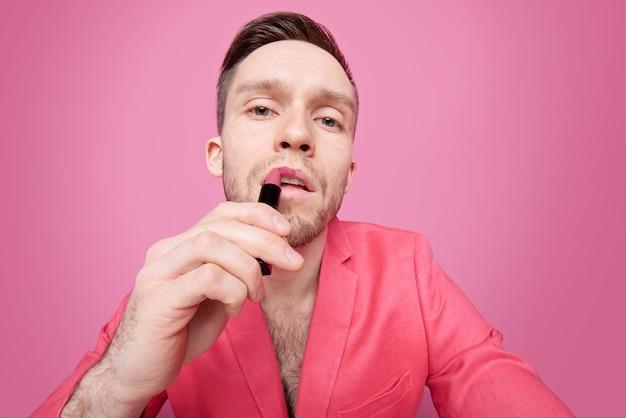 Giovane uomo affascinante rilassato in accappatoio rosso che applica rossetto rosa sulle labbra mentre era seduto in isolamento