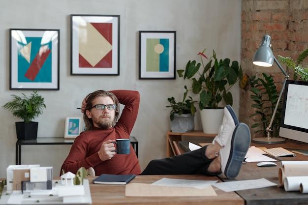 Giovane architetto maschio rilassato con una tazza di caffè che ti guarda mentre è seduto davanti alla telecamera e pensa a idee per un nuovo progetto