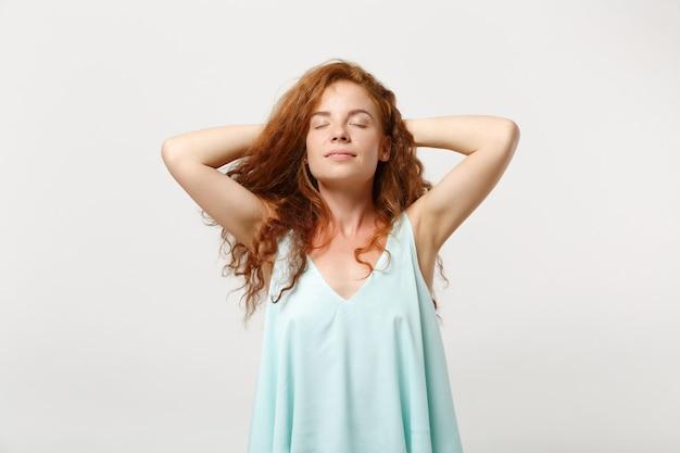 Giovane donna rilassata della testarossa in vestiti leggeri casuali che posano isolato sul fondo bianco della parete in studio. concetto di stile di vita di emozioni sincere della gente. mock up copia spazio. dormi con le mani dietro la testa.