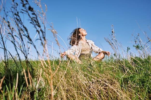 Giovane donna rilassata con i capelli ondulati lunghi scuri che attraversano le gambe mentre era seduto nell'erba verde contro il cielo blu e godendo del riposo in una giornata di sole