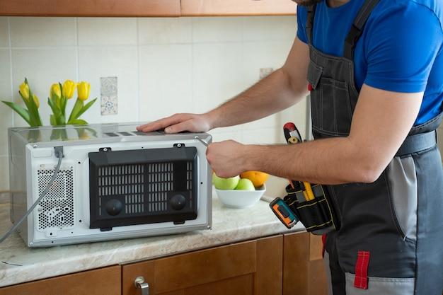 Giovane riparatore che fissa e ripara il forno a microonde con un cacciavite in cucina