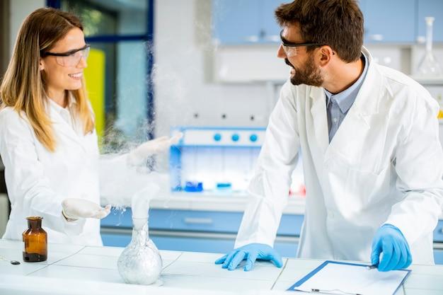 Giovani ricercatori che fanno esperimenti con il fumo su un tavolo di un laboratorio chimico