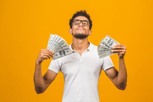 Giovane uomo afroamericano ricco in maglietta casuale che tiene le fatture del dollaro dei soldi