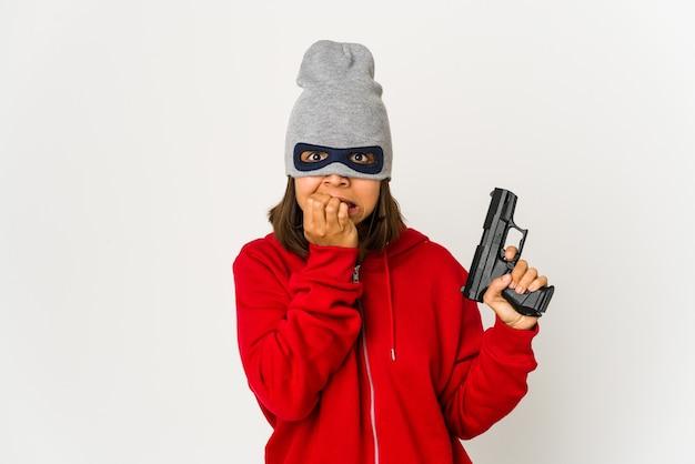 Giovane donna ispanica rapinatrice che indossa una maschera mordendosi le unghie, nervosa e molto ansiosa