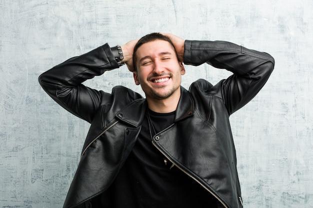 Il giovane uomo dell'attuatore ride con gioia tenendo le mani sulla testa. concetto di felicità.