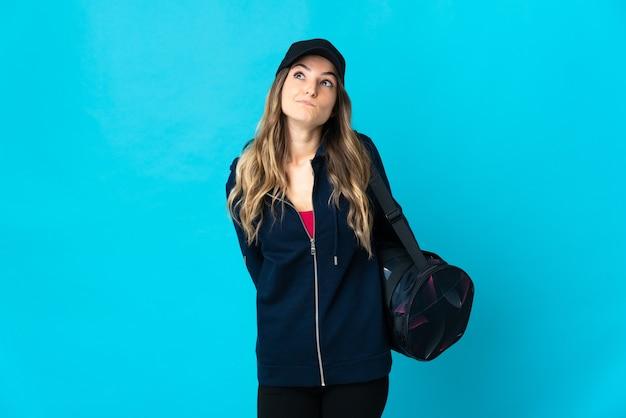 Giovane donna rumena di sport con borsa sportiva isolata su sfondo blu e alzando lo sguardo
